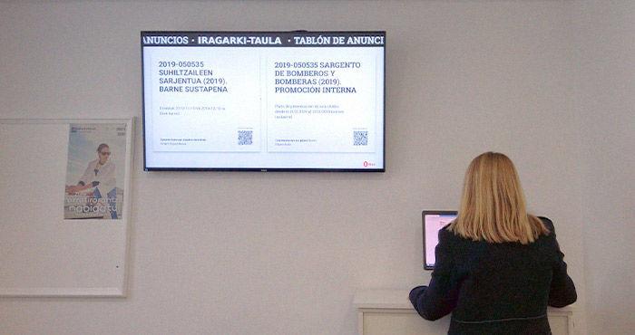 Mujer utilizando ordenador junto a pantalla